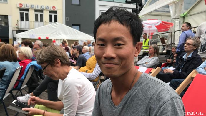 Beethovenfest 2018 (DW/R. Fulker) Man in a grey T-shirt smiles while sitting in Bonn main square.