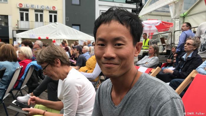 Beethovenfest 2018 (DW/R. Fulker) Asiatischer Mann im grauen T-Shirt sitzt am Bonner Marktplatz