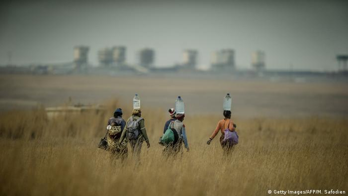 Women carrying water near the Secunda fuel plant