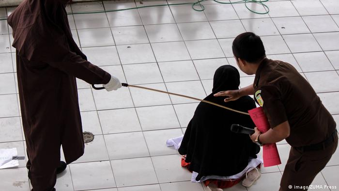 Woman being caned for alleged prostitution in Indonesia