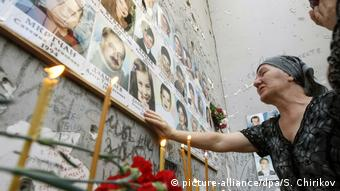 Survivors in the northern Caucasus city of Beslan light candels to commemorate the victims of the siege at a school which killed more than 330 people