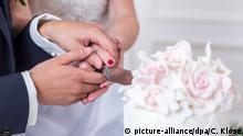ILLUSTRATION - Ein Mann und eine Frau stehen am 04.07.2018 in einer Wohnung in Hamburg und schneiden gemeinsam die Hochzeitstorte an (gestellte Szene). Foto: Christin Klose | Verwendung weltweit