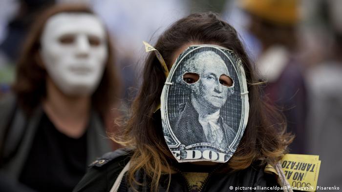 Pessoa usa máscara com pedaço de cédula de dólar