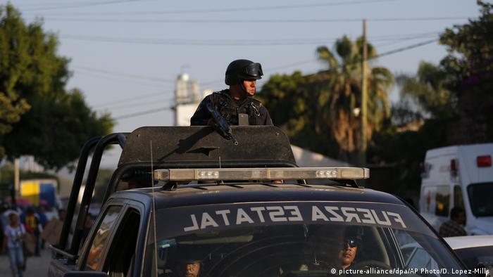 Policial com capacete sobre um veículo patrulhando região do México