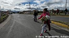 Venezuelan migrant Mariangela Ascano walks along the Pan-American Highway in Ipiales, Colombia, on her way to Ecuador, on August 23, 2018. - Ascano, 21, mother of a two-year-old boy and with a pregnancy of two months, left Maracay 20 day ago with the goal of reaching Quito. (Photo by Luis ROBAYO / AFP) (Photo credit should read LUIS ROBAYO/AFP/Getty Images)