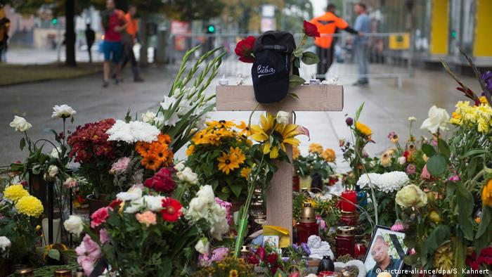 Flowers and a wooden cross at a memorial for Daniel H. in Chemnitz