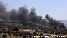 04.09.2018 A picture taken on September 4, 2018 shows smoke blowing from buildings on fire that were hit by reported Russian air strikes in the rebel-hold town of Muhambal, about 30 kilometres southwest of the city of Idlib. - Russian warplanes battered Syria's rebel-controlled northwestern Idlib province on September 4 for the first time in three weeks, the Syrian Observatory for Human Rights reported, as fears of a government offensive mount. (Photo by OMAR HAJ KADOUR / AFP) (Photo credit should read OMAR HAJ KADOUR/AFP/Getty Images)