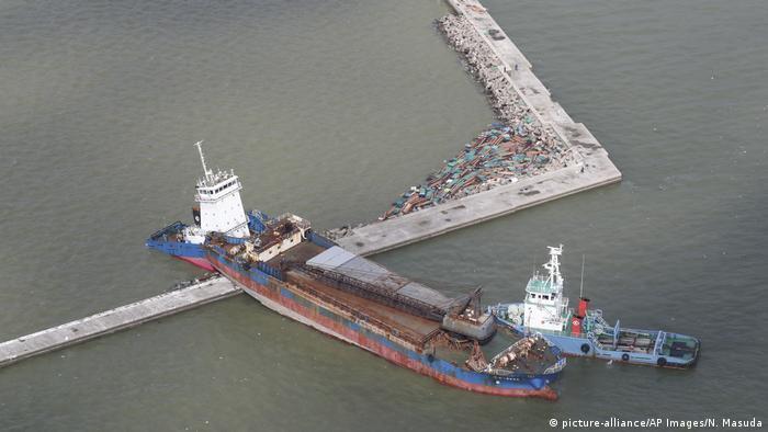 A large vessel stuck on a breakwater