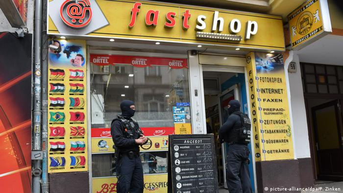 Police stance outside a kiosk in Berlin that they had raided on suspicion of illegal weapons possession