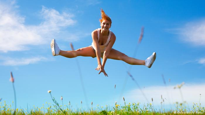 Smiling woman doing an acrobatic jump on a grassy field for fun (Colourbox/V. Koval)