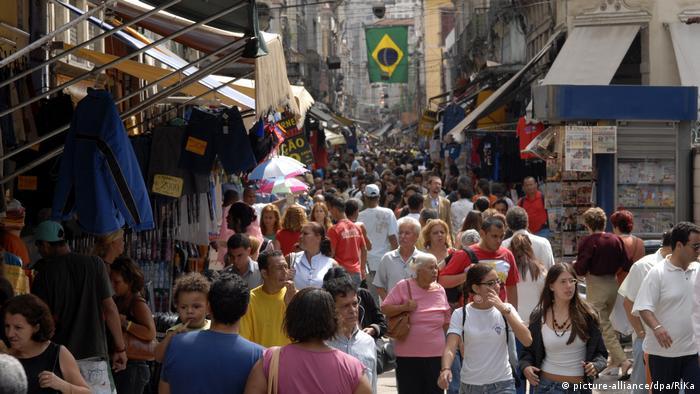 Pessoas em calcadão com bandeira do Brasil ao fundo