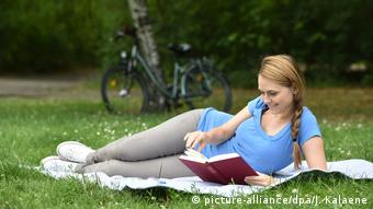 A woman lying on a picnic blanket with a book (picture-alliance/dpa/J. Kalaene)