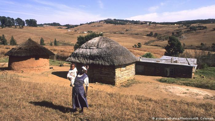 A grandmother stands holding a young child in front of a small village near Mbabane, the capital of Swaziland - now known as eSwatini,