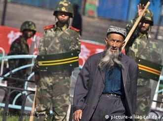 Troops watch a Uighur man in Urumqi, the capital of Xinjiang province