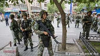 Police squads patrol the streets of Urumqi after the riots last year