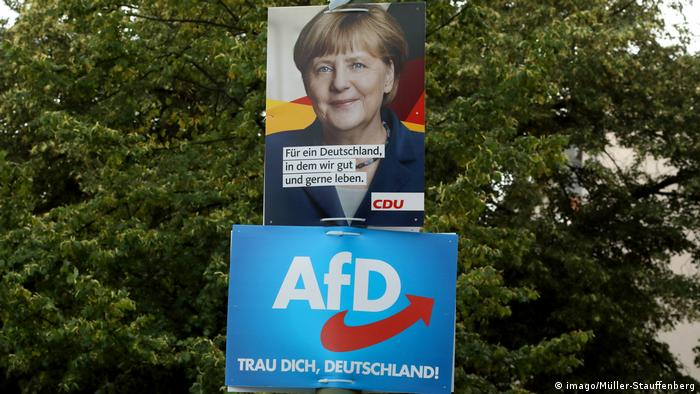 A poster of Merkel for the CDU is attached to a post above an AfD poster during the 2017 parliamentary election campaign
