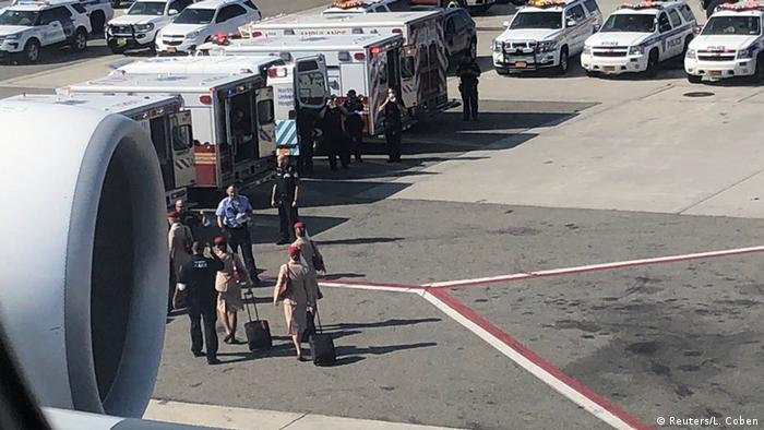 Air cabin crew members and the emergency services are seen leaving the plane after passengers were taken ill on a flight from Dubai to New York