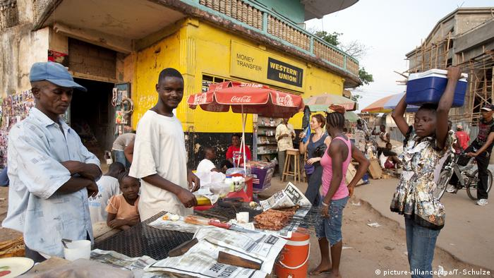 Traders sells meat skewers and other items in a busy street in Makeni, Sierra Leone