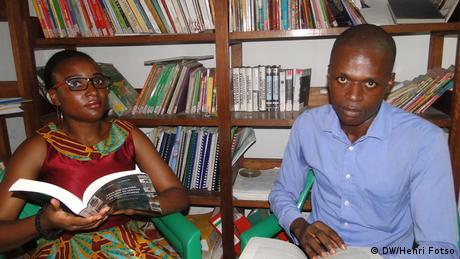 Marie-Joseph Ekobena and Philemon Moubeke sitting in front of bookshelves and holding books (DW/Henri Fotso)