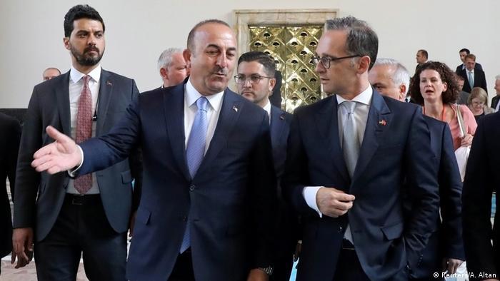 German foreign minister and Turkish counterpart Mevlut Cavusoglu walk around the Turkish Parliament in Ankara