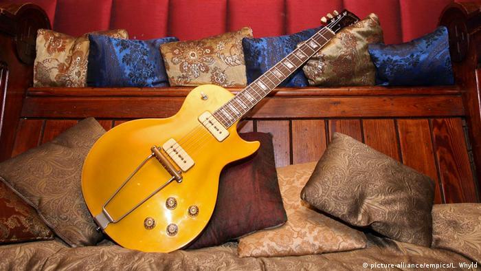 Alte Gibson Les Paul Gitarre, die einst Erc Clapton gehörte auf einer Holzbank mit Sofakissen