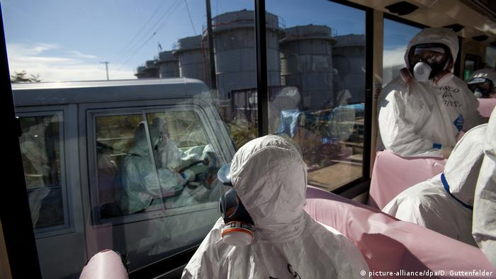 Officials from the Tokyo Electric Power Co. and Japanese journalists look out from bus windows as workers pass by in a van inside the grounds of the crippled Fukushima nuclear power plant