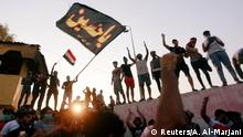 Iraqi protesters stand on concrete blast walls during a protest near the building of the government office in Basra