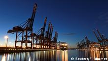 A container ship docks in the dusk at Hamburg Port