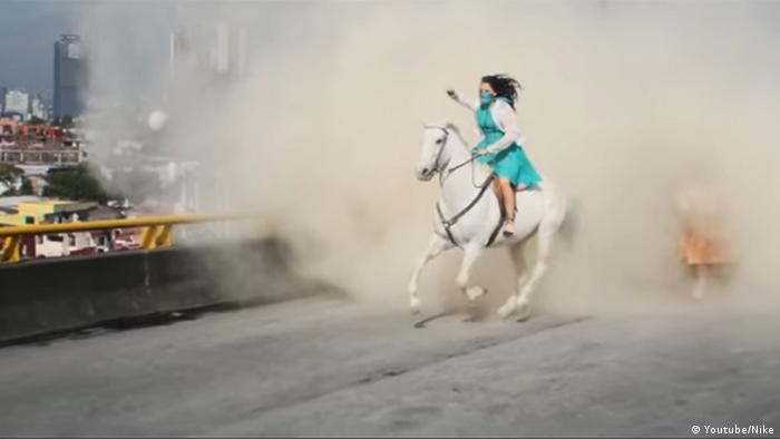 Video still from Nike ad: Woman on white horse with green dress and scarf (Youtube/Nike)