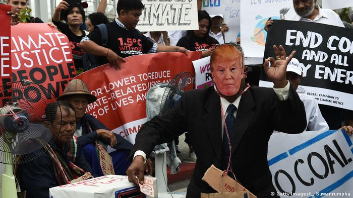 An environmental activist wearing a face mask depicting US President Donald Trump takes part in a demonstration in front of the United Nations building in Bangkok, Thailand