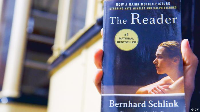 A hand holds the book The Reader, which shows the side profile of a boy's fac