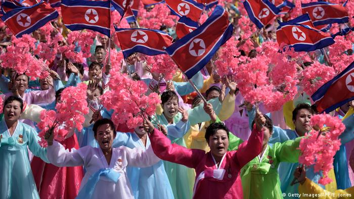 Participants wave flowers as they march past a balcony from where North Korea's leader Kim Jong Un was watching the celebrations