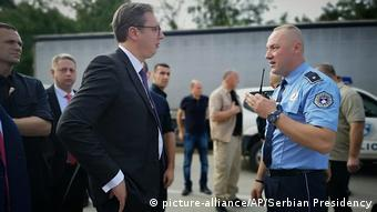 A Kosovo police officer stops Serbian President Aleksandar Vucic from continuing his trip to the village of Banje
