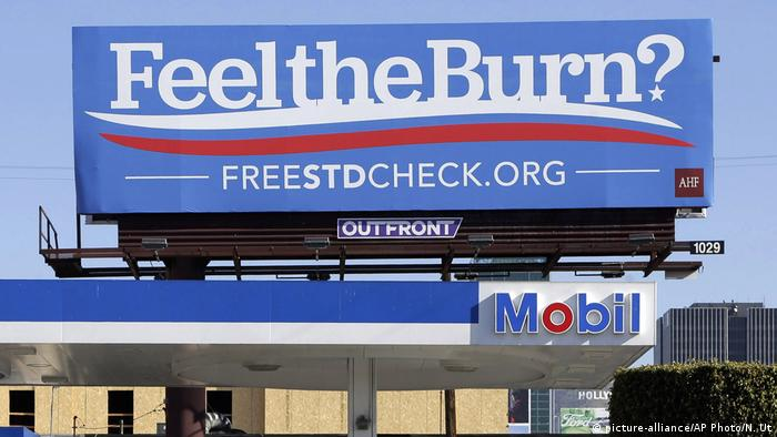 Billboard above a gas station that reads Feel The Burn promoting testing for sexually transmitted diseases