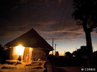 A house in an African village, illuminated by electric light. Foto by Gideon Mendel (CORBIS).