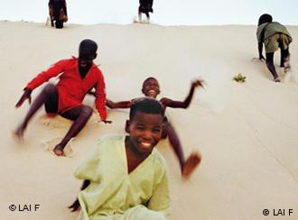 Children playing on a dune. Foto by Berthold Steinhilber (LAIF)
