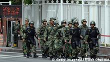 Chinese paramilitary police patrol a street in Urumqi, the capital of Xinjiang province
