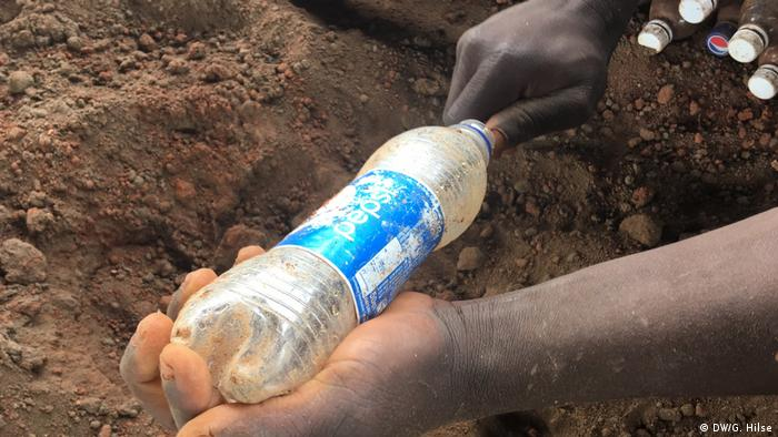 A plastic bottle being filled with soil