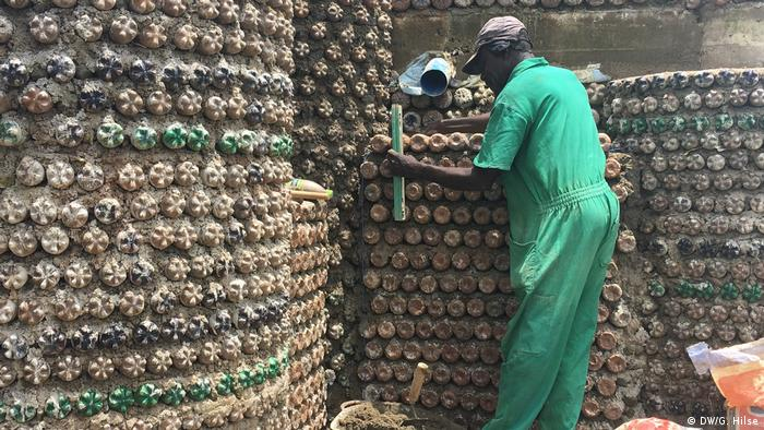 A man in green overalls plasters a wall made of bottles Abuja
