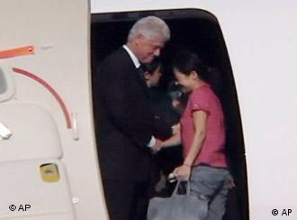 In this image taken from a footage shot by APTN, former US president Bill Clinton, left, greets one of two US journalists, Euna Lee, right, as they board a plane to depart for home at an airport in Pyongyang, North Korea, Wednesday, Aug. 5, 2009. (AP Photo/APTN)