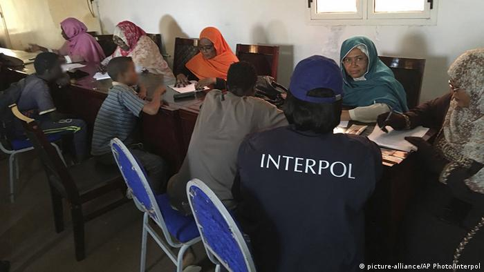 An Interpol agent sits next to several of the victims and Sudanese aid workers
