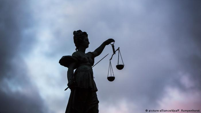A silhouette of a statue of Justitia