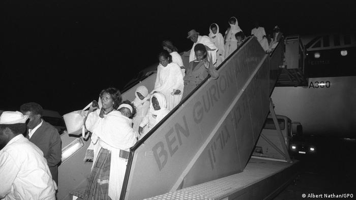 A black and white photo shows Ethiopian Jews disembarking a plane at night during 'Operation Solomon'