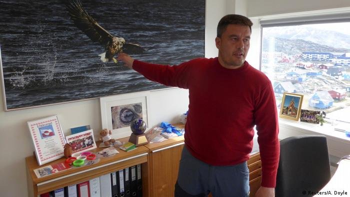 Greenland Prime Minister Kim Kielsen stands in his office with a giant photograph of a sea eagle in Nuuk.