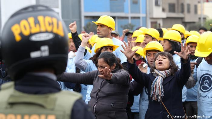 Peruvian evangelicals hold out their hands in a group in front of police (picture-alliance/ZumaPress)