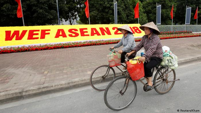 Two Vietnamese women ride their bicycles past a WEF ASEAN sign