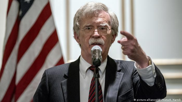 Bolton gestures in front of a podium