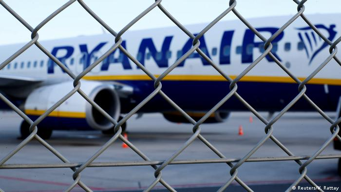 A Ryanair plane behind a fence on the tarmac of an airport (Reuters/W. Rattay)