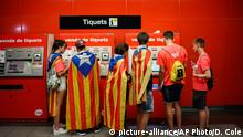 Youth carrying Catalan pro-independence flags on their shoulders get tickets for the subway on their way to a demonstration marking the Catalan National Day in Barcelona, Spain, Tuesday, Sept. 11, 2018. Catalan authorities have made a call to flood the streets of Barcelona later on Tuesday. Sept. 11, called Diada, marks the fall of the Catalan capital to Spanish forces in 1714. (AP Photo/Daniel Cole) |