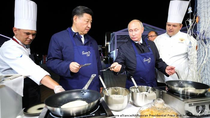 Russian President Vladimir Putin and China's Xi Jinping toss pancakes on the sidelines of the Eastern Economic Forum in Vladivostok